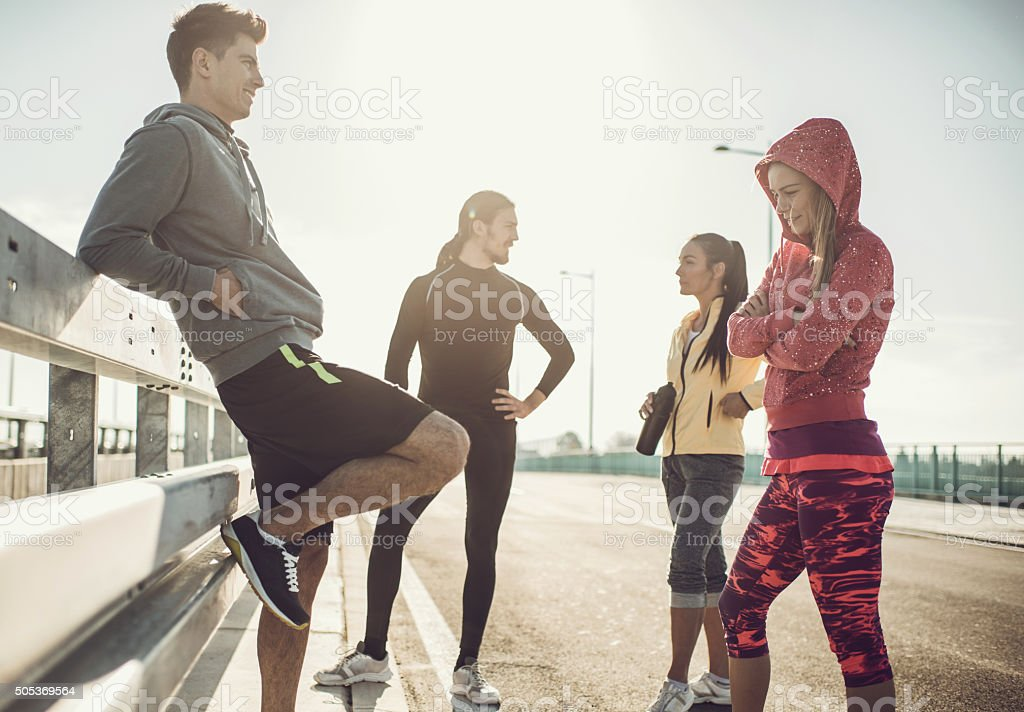 Smiling friends taking a break from exercising and communicating. stock photo