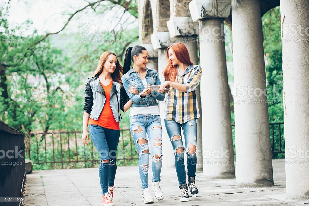 Smiling friends talking and walking together outdoor stock photo