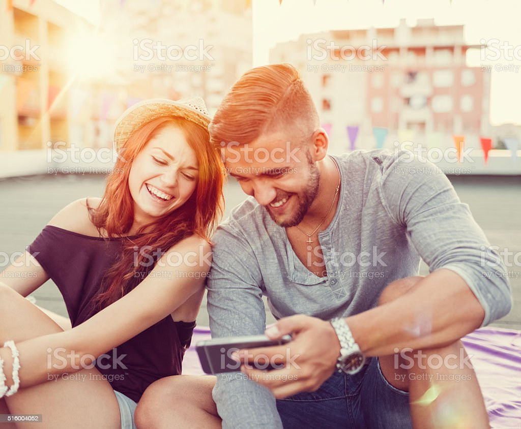 Smiling friends using smartphone to watch tv stock photo