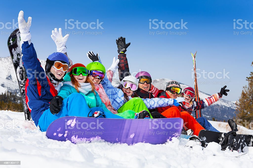 Smiling friends wearing goggles with hands up stock photo