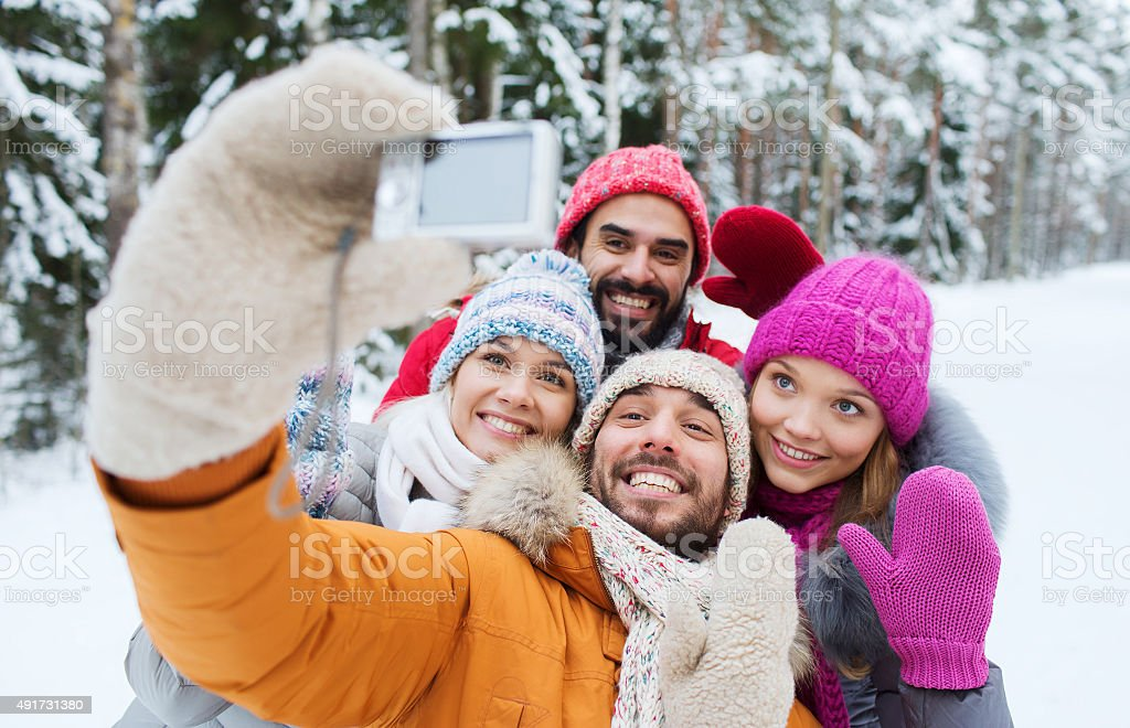 smiling friends with camera in winter forest stock photo