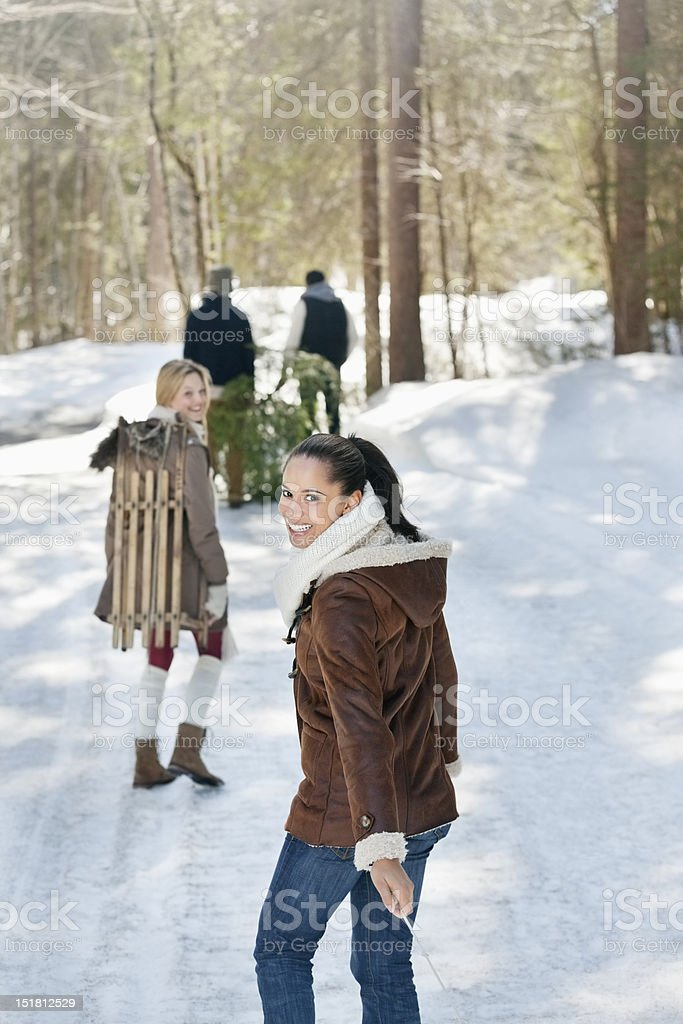 Smiling friends with fresh cut Christmas tree and sled in snowy woods royalty-free stock photo