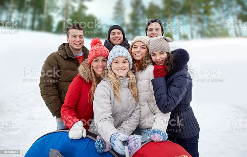 smiling friends with snow tubes and selfie stick stock photo
