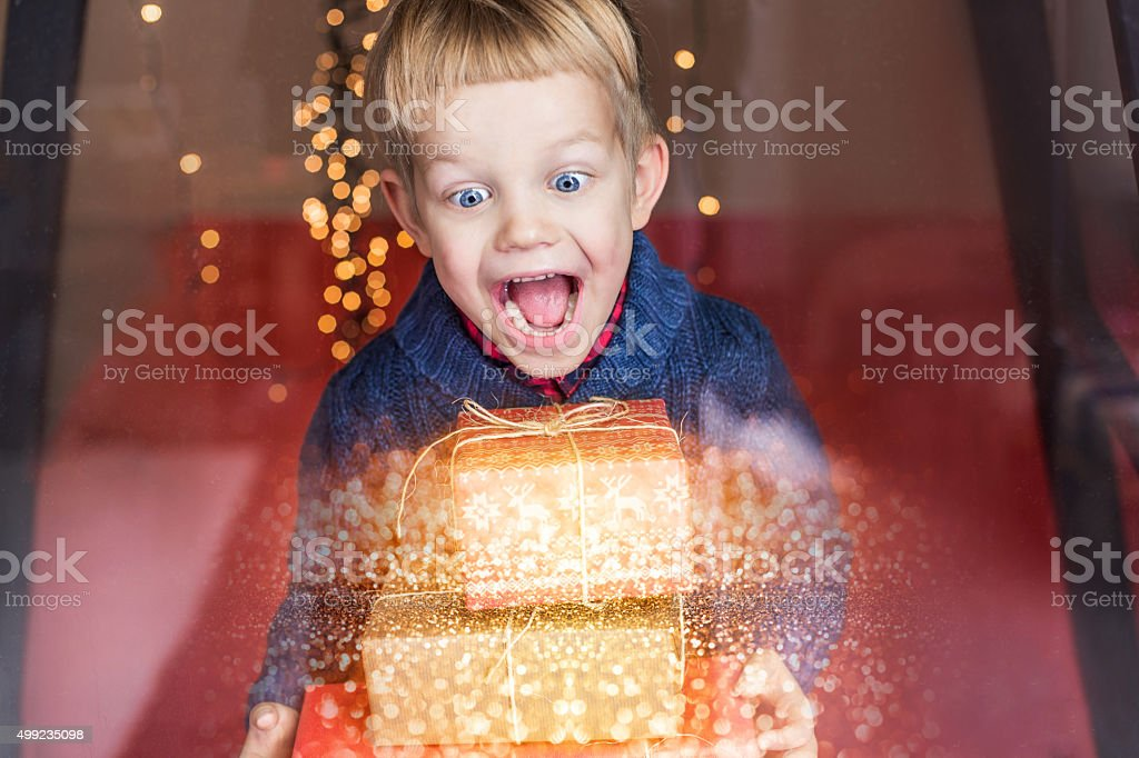 Smiling funny child holding Christmas gift in hand. Christmas concept stock photo