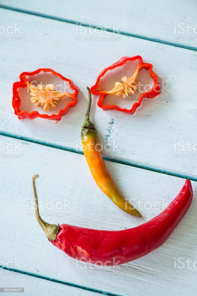 Smiling funny face made with hot chilli peppers on wood stock photo