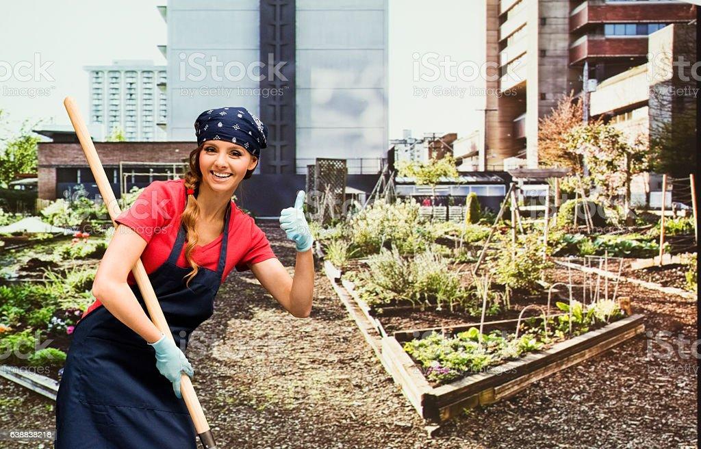Smiling gardener giving thumbs up in garden stock photo