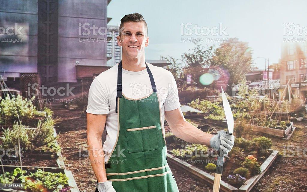 Smiling gardener holding shovel in garden stock photo
