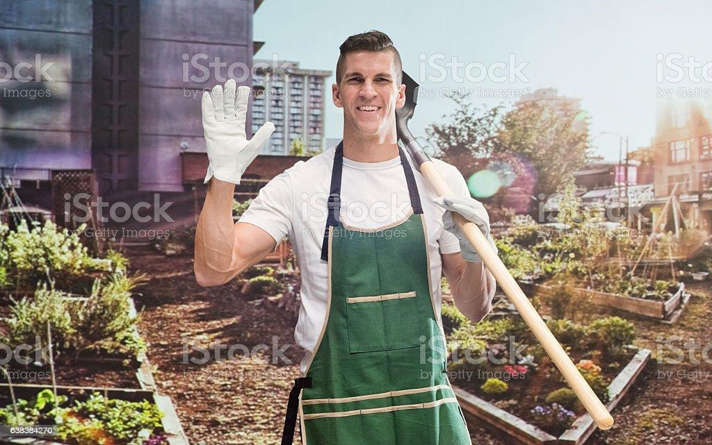 Smiling gardener waving hand in garden stock photo