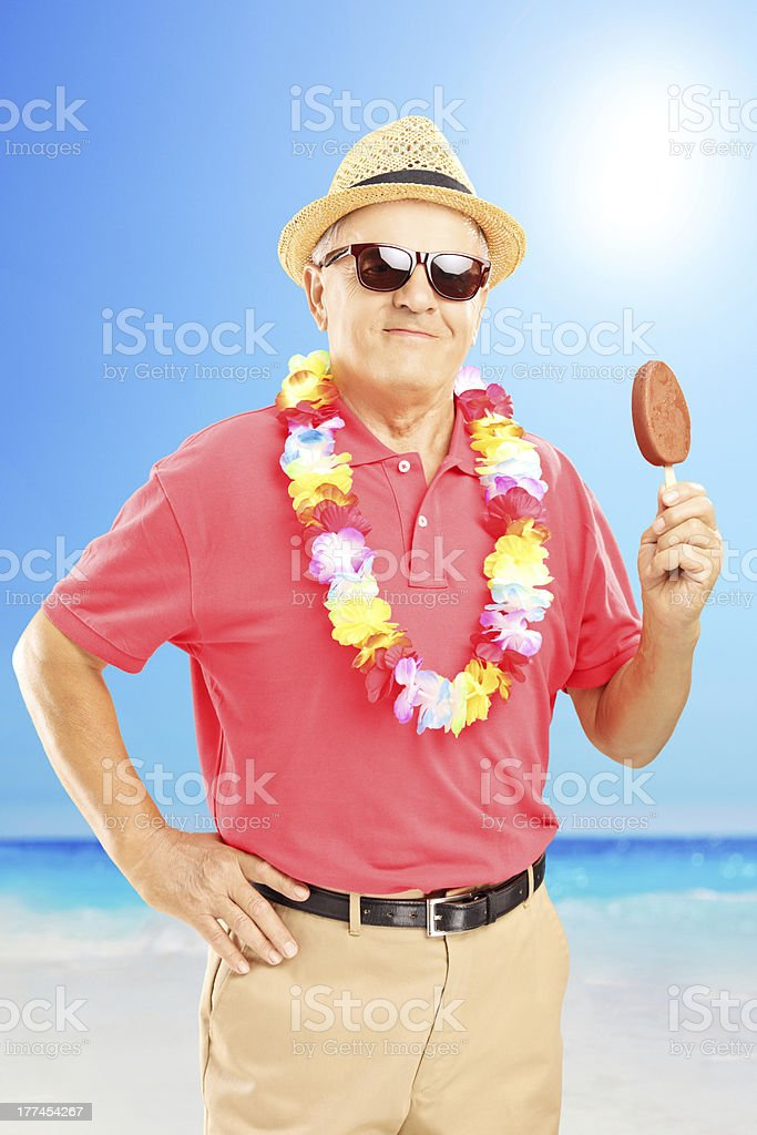Smiling gentleman with hat eating ice cream on a beach royalty-free stock photo