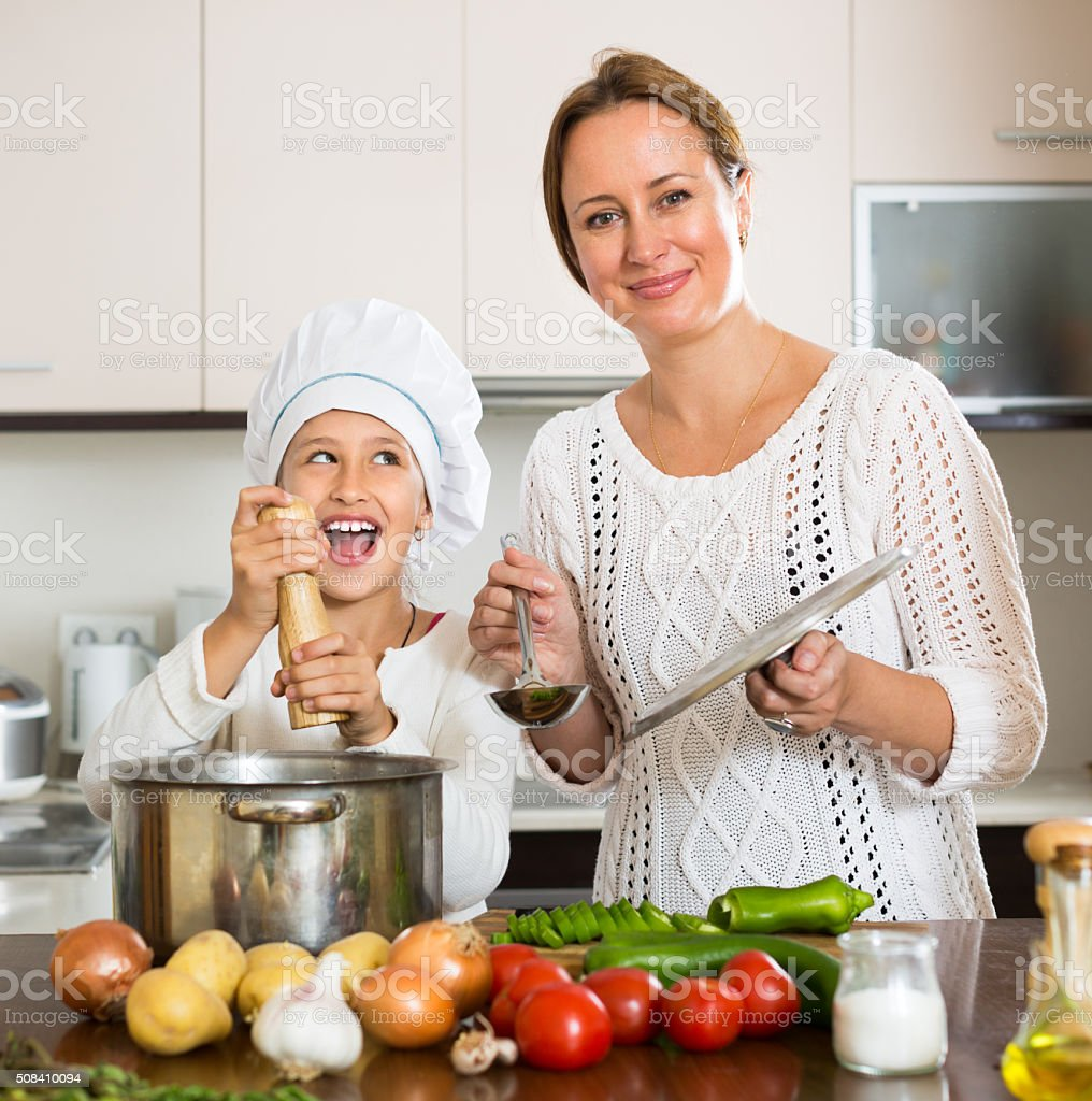 Smiling girl and mom at kitchen stock photo