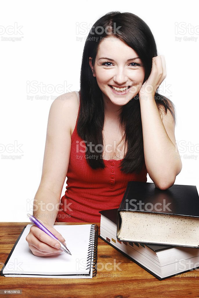 Smiling girl at desk writing on a notepad royalty-free stock photo