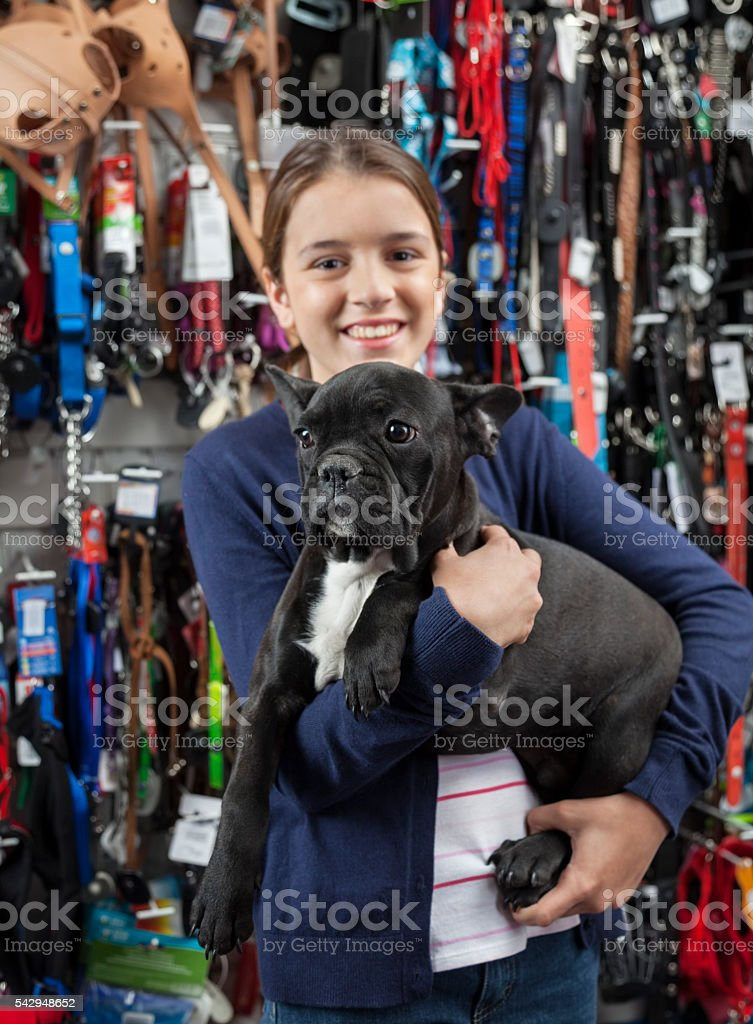 Smiling Girl Carrying French Bulldog In Store stock photo