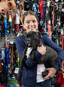 Smiling Girl Carrying French Bulldog In Store