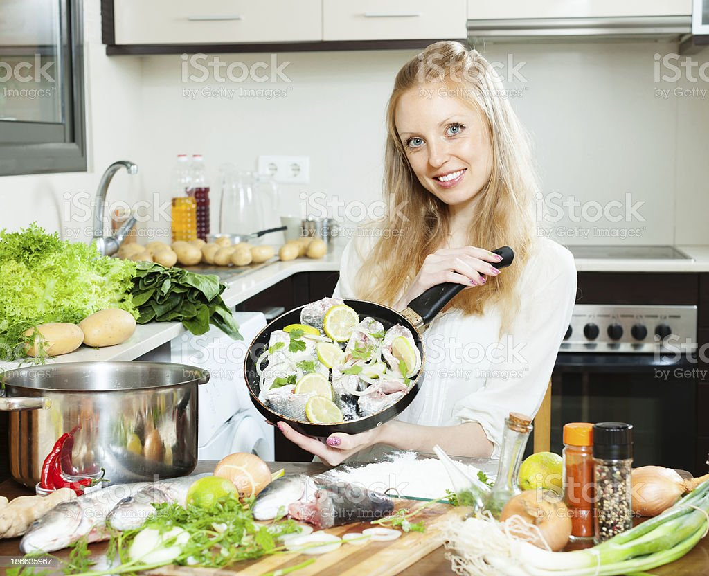 Smiling girl cooking fish  in frying pan stock photo