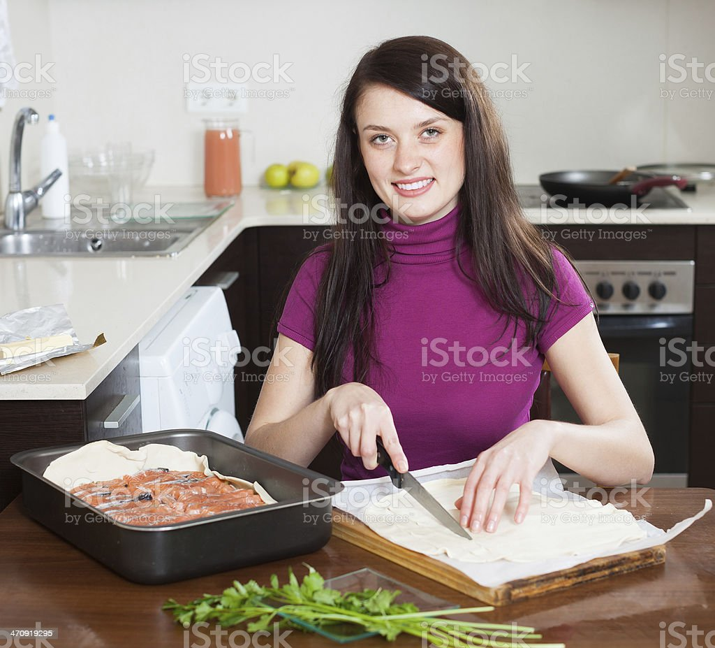 Smiling girl cooking fish pie stock photo