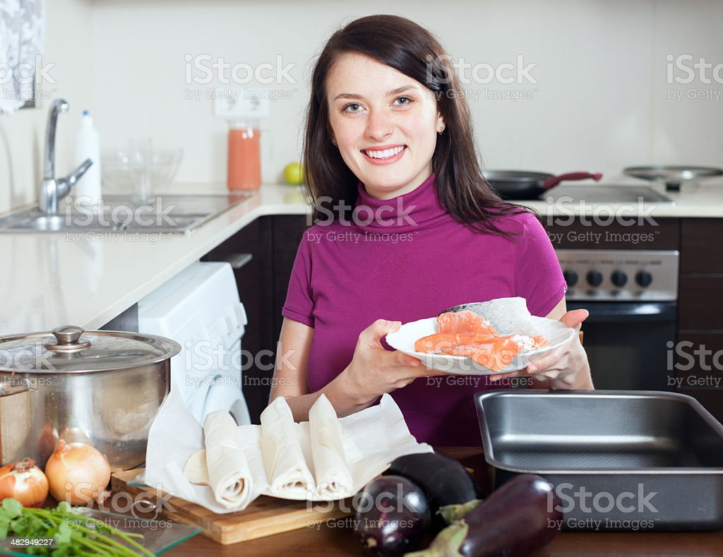 Smiling girl cooking fish pie with  salmon stock photo