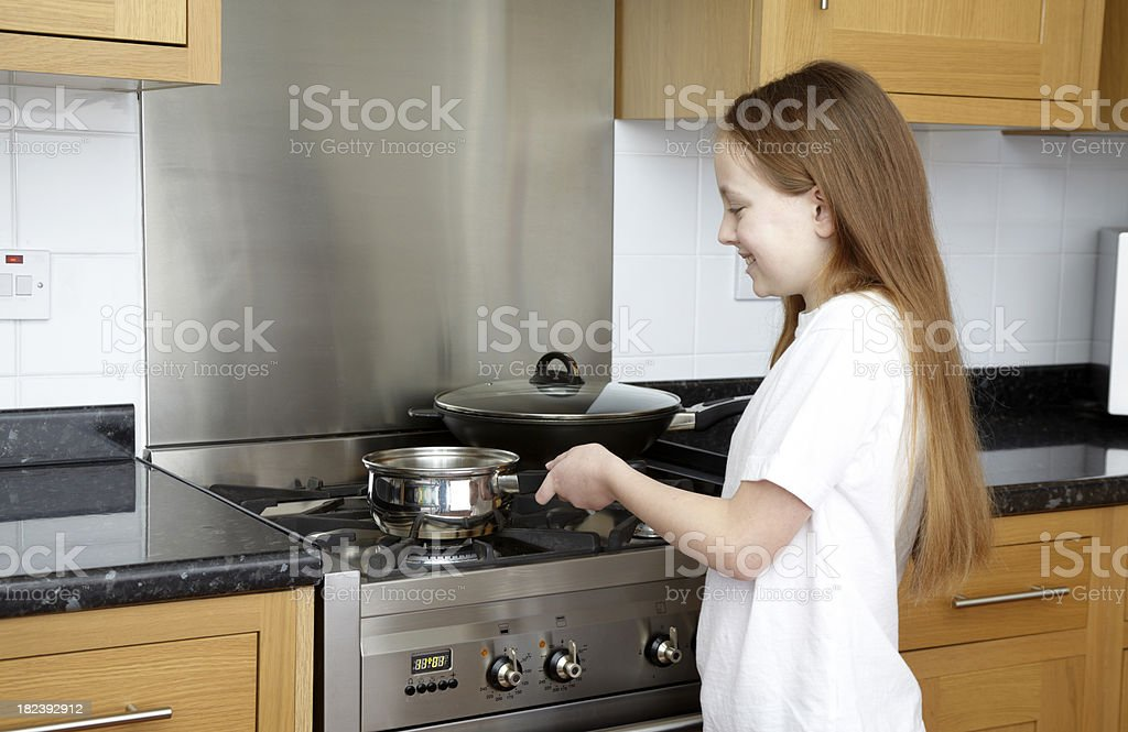 Smiling Girl cooking with pan in modern kitchen stock photo