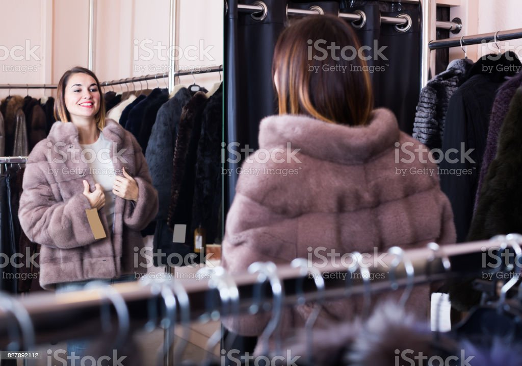 Smiling girl deciding on the choice of fur coat stock photo
