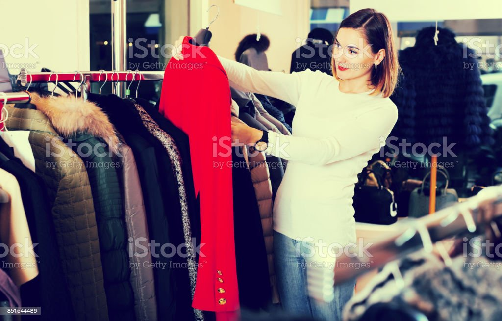Smiling girl deciding on warm red coat stock photo