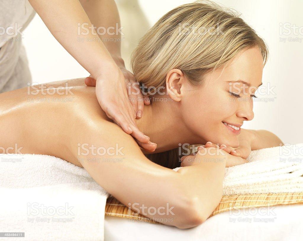 Smiling girl enjoying a shoulder massage stock photo