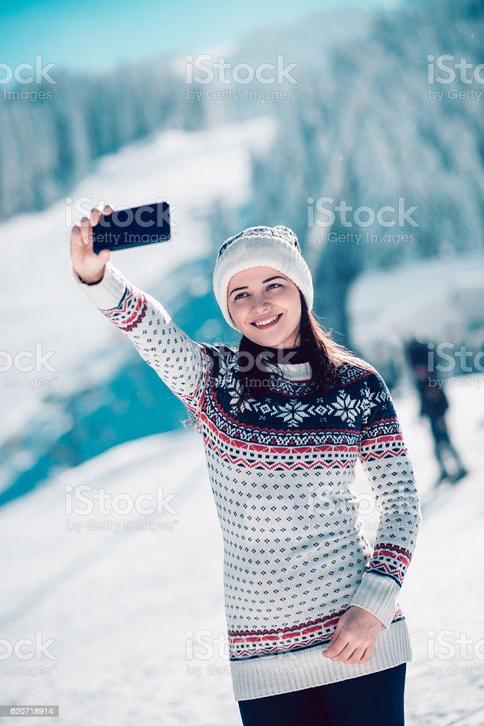 Smiling Girl Enjoying Winter and Taking Selfie while Snowing stock photo