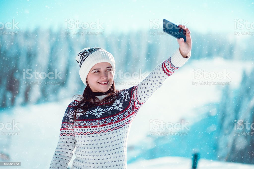 Smiling Girl Enjoying Winter and Taking Selfie while Snowing stock photo