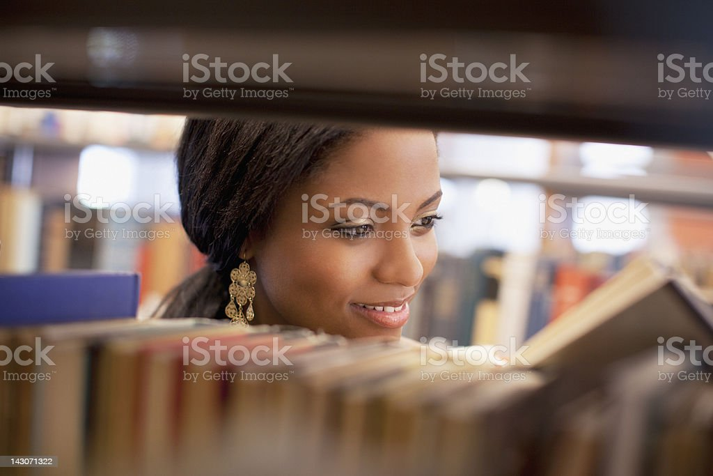 Smiling girl examining book in library royalty-free stock photo