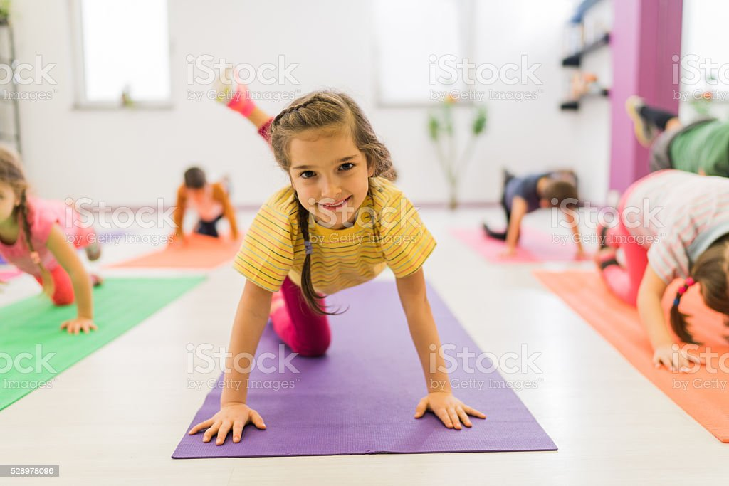 Smiling girl exercising on a sports training at health club. stock photo