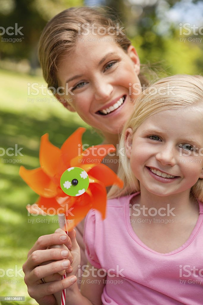 Smiling girl holding a pinwheel with her mother stock photo
