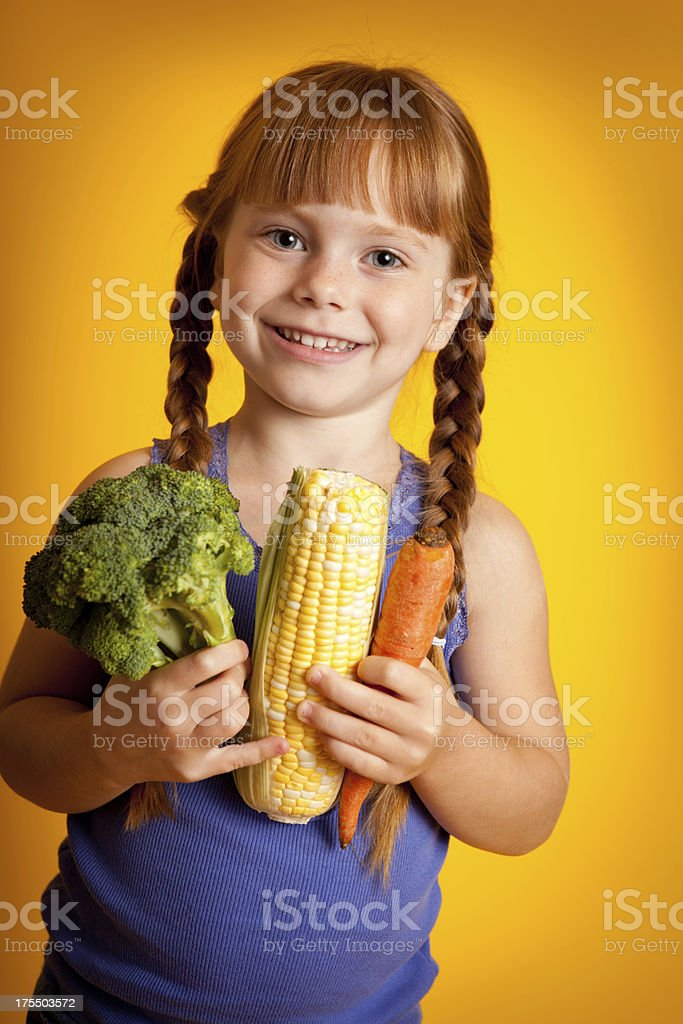 Smiling Girl Holding an Armful of Vegetables royalty-free stock photo