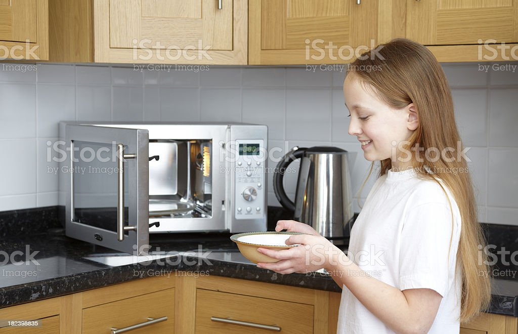 smiling girl holding bowl cooking with microwave oven in kitchen stock photo