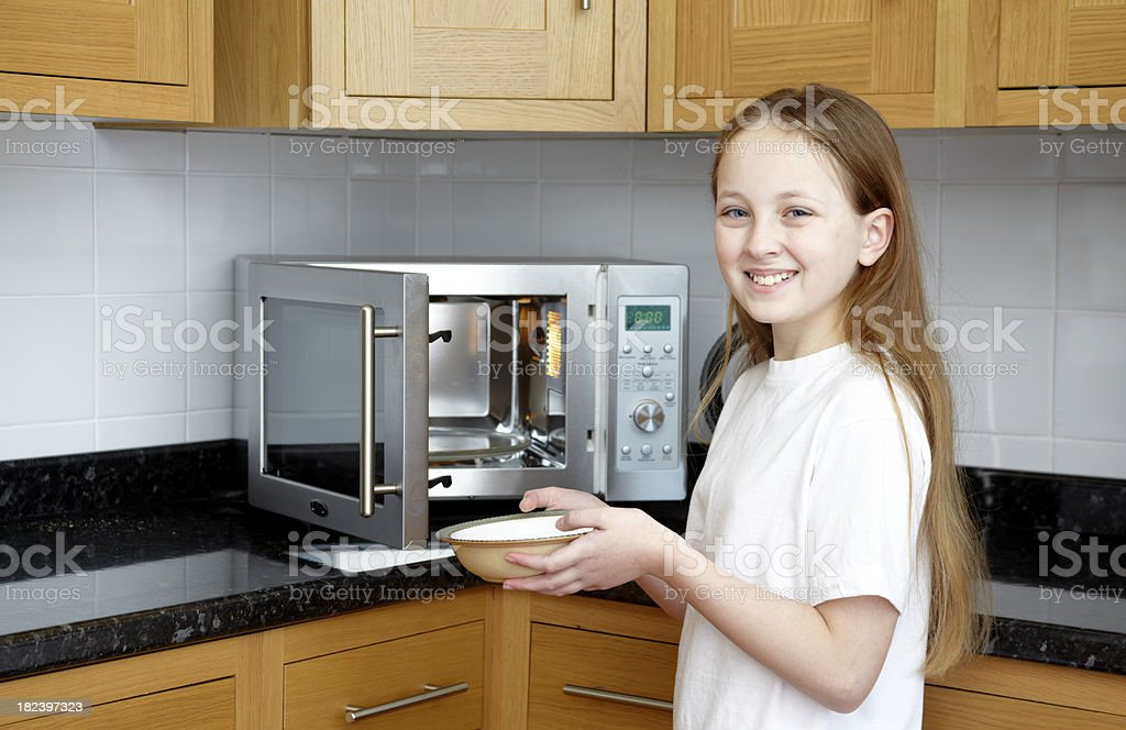 Smiling Girl holding bowl with microwave doing domestic kitchen chore stock photo