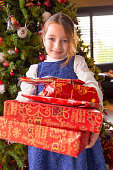 Smiling girl holding Christmas gifts