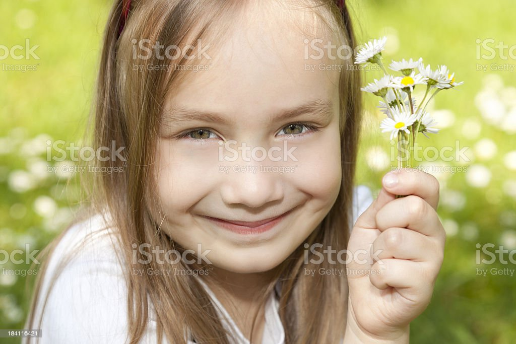 Smiling girl holding flowers outdoors royalty-free stock photo