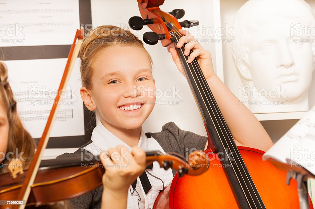 Smiling girl holds cello with other friend near stock photo