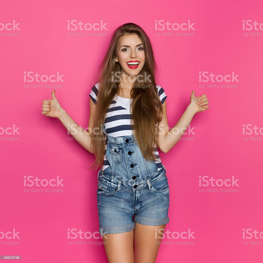 Smiling Girl In Dungarees Showing Thumbs Up stock photo