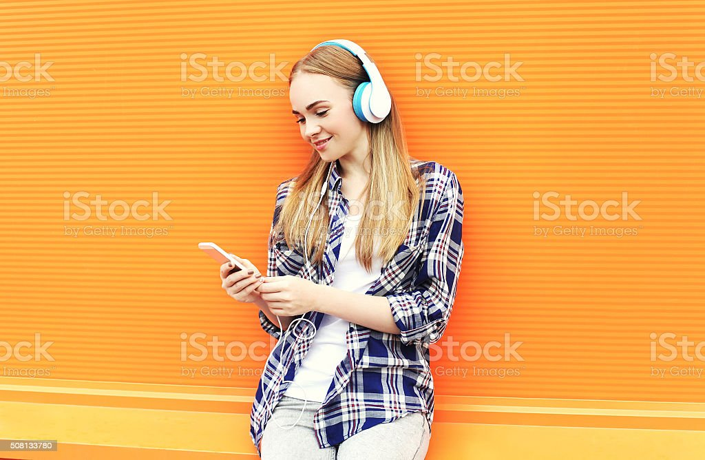 Smiling girl in headphones listens to music and using smartphone stock photo