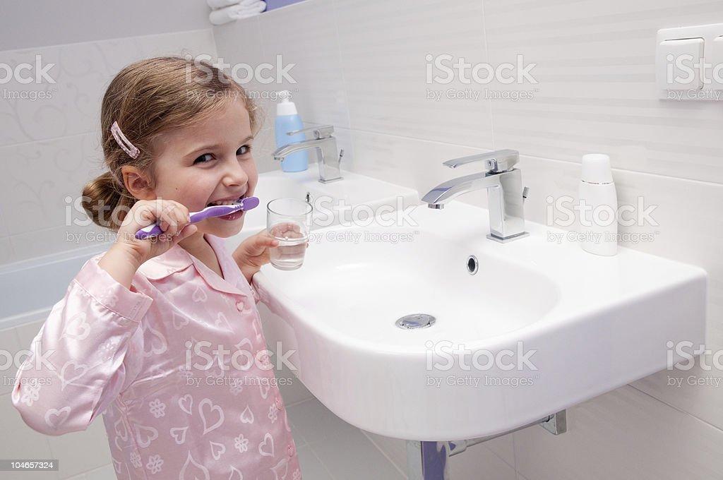 Smiling girl in pink pajamas brushing teeth at the sink stock photo