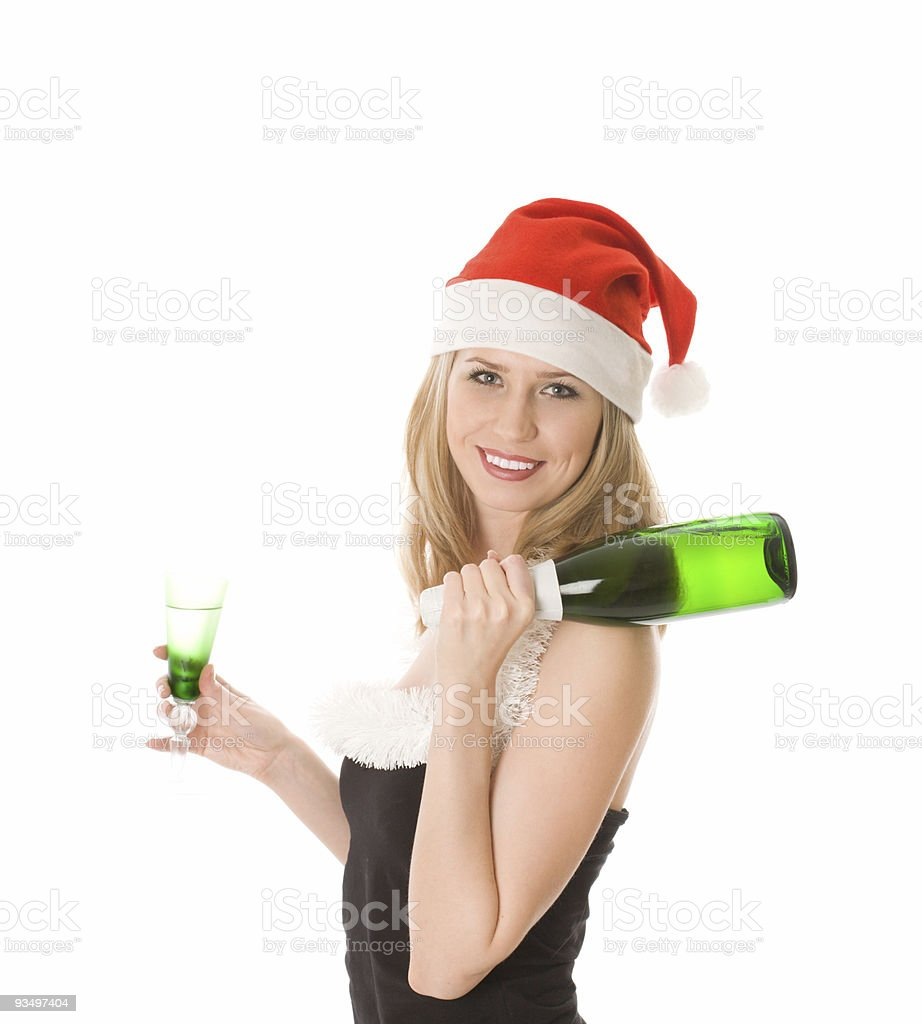 Smiling girl in red santa hat holding glass and bottle stock photo