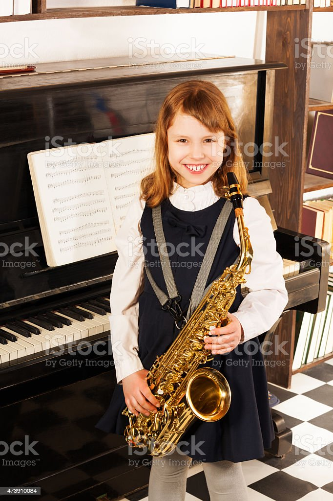 Smiling girl in school uniform with alto saxophone stock photo