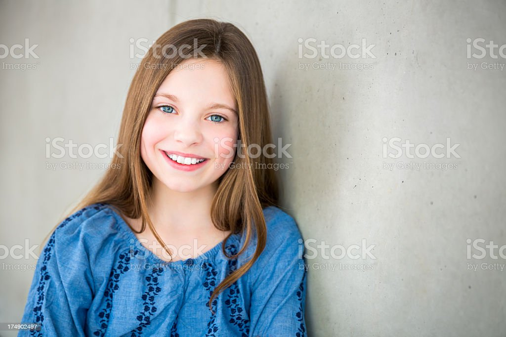 Smiling Girl leaning against wall looking at camera royalty-free stock photo