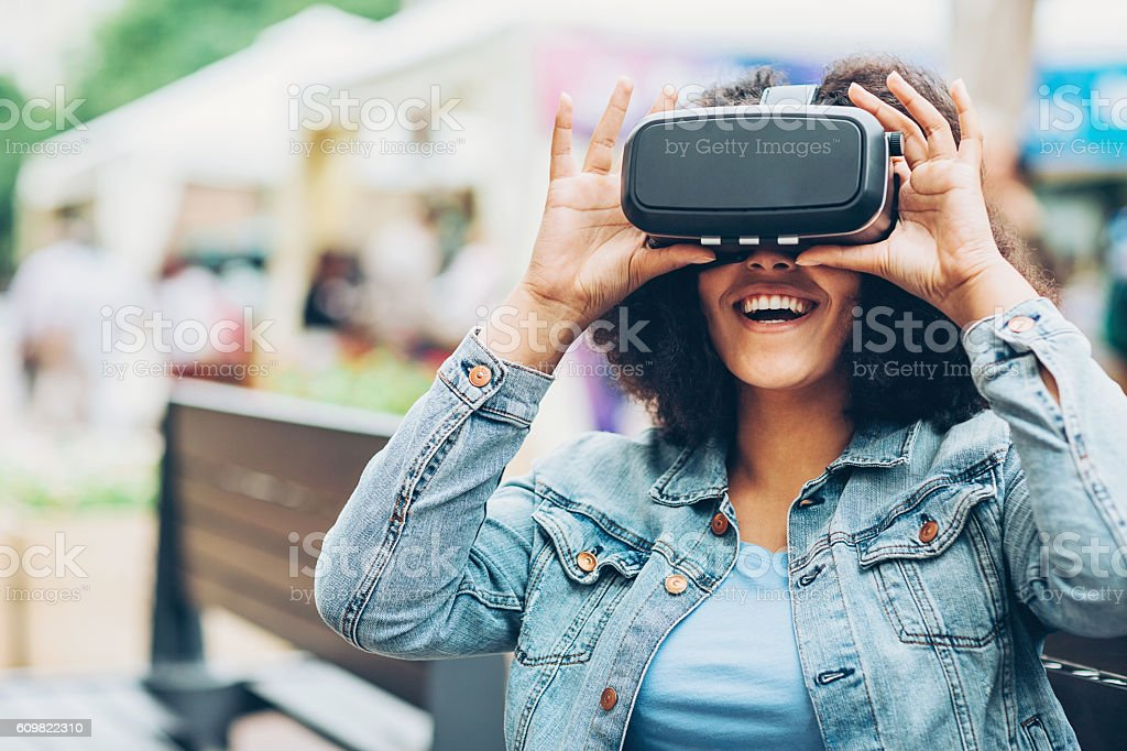 Smiling girl looking through a virtual reality headset stock photo