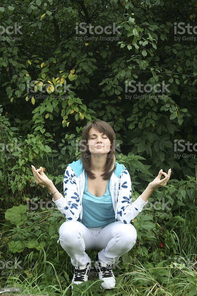 Smiling girl meditating in a forest royalty-free stock photo