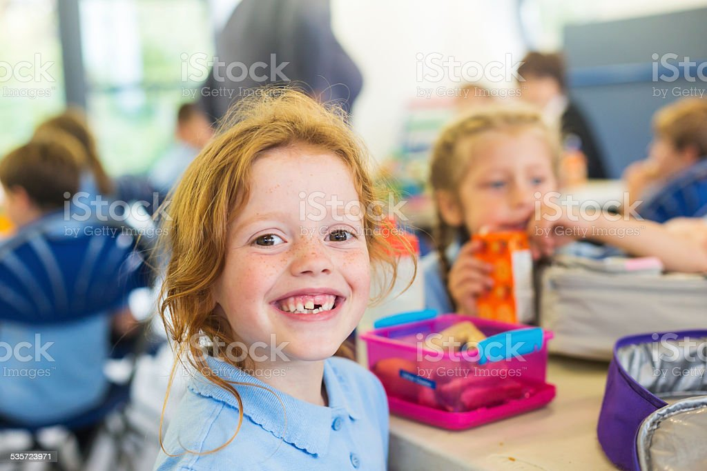 Smiling Girl Missing a Tooth With a Healthy Lunch stock photo