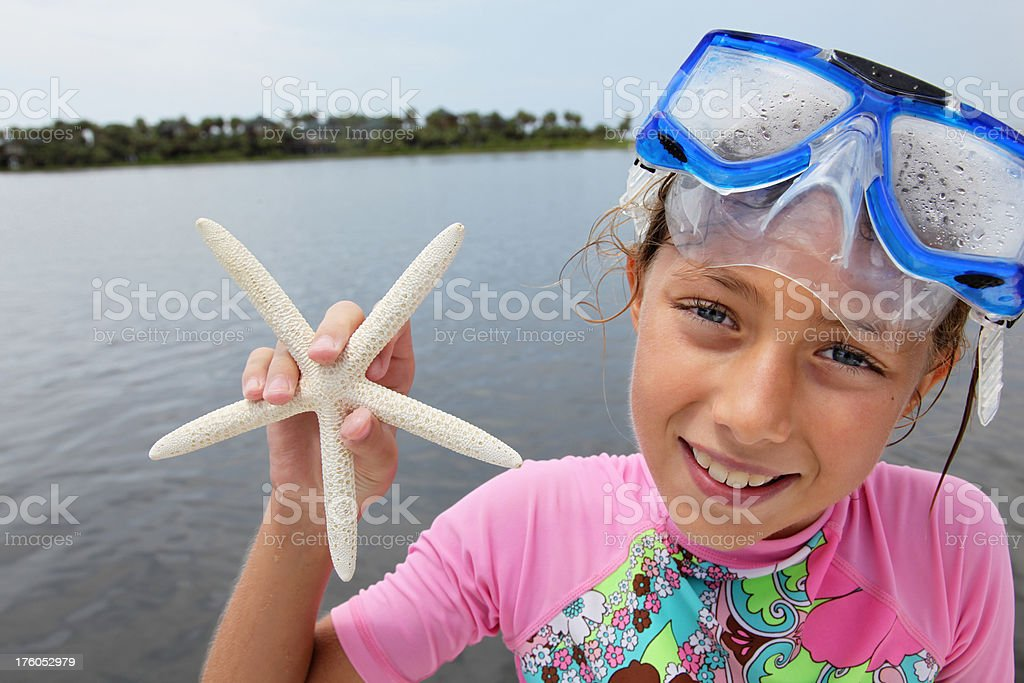 Smiling Girl on Vacation holding Starfish stock photo