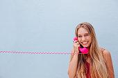 Smiling girl on vintage telephone