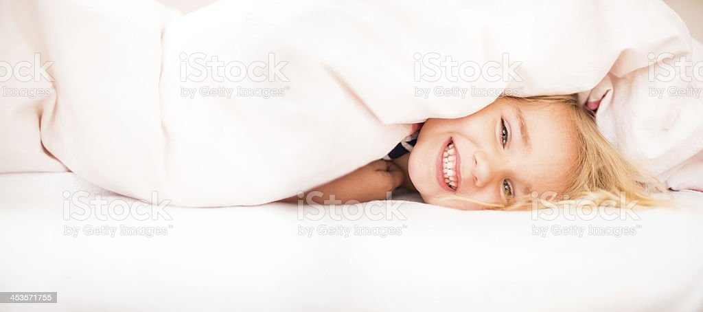 Smiling girl peeking under blanket royalty-free stock photo