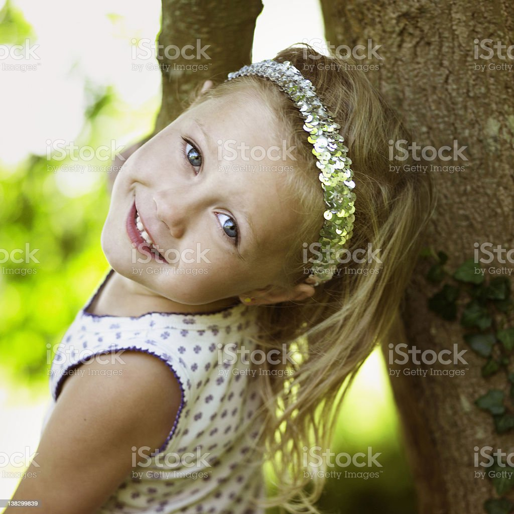 Smiling girl playing in tree stock photo