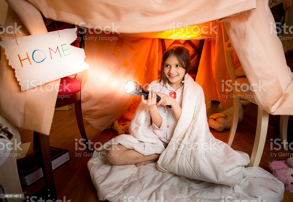smiling girl playing with flashlight in house made of blankets stock photo
