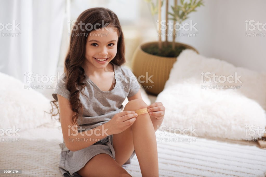 Smiling girl putting band aid on knee at home stock photo